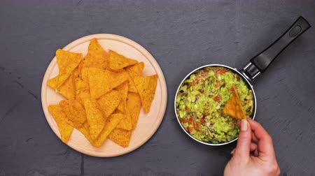 Making guacamole for a tortilla chips snack - stop motion animation, top down view
