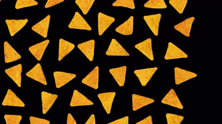 Delicious tortilla chips march across screen - stop motion like animation, isolated on black, easy to change background