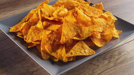 Tortilla chips filling a rotating rectangular plate - stop motion animation, side view