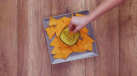 Hands taking delicious tortilla chips from a rotating rectangular plate with guacamole in the center - fast food concept, time lapse