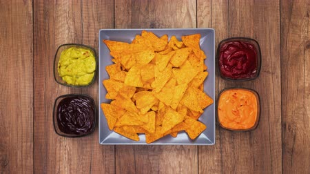 Tortilla chips filling a rotating rectangular plate with assorted sauces slide in - stop motion animation