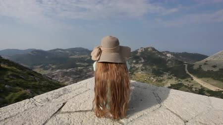 Girl on mountain top sit and admire the view on a beautiful sunny summer day Stok Video