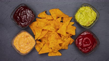Tortilla chips piling up then disappearing from a black slate surface surrounded by a variety of sauces - stop motion animation Stok Video