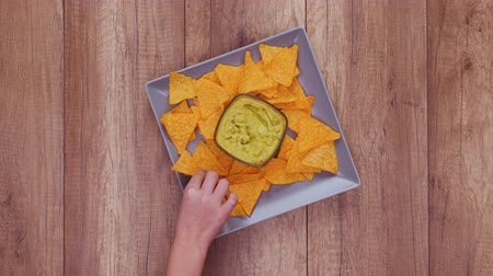 Hands taking delicious tortilla chips from a rotating rectangular plate with guacamole in the center. People eating together, sharing food.