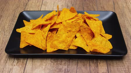 Tortilla chips filling then disappearing from a rectangular plate leaving a large black copy space - stop motion animation, side view