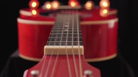 Camera slide along the neck of a red acoustic guitar - musical instrument detail, shallow depth