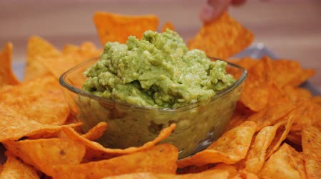 Hands taking delicious tortilla chips from a plate with guacamole in the center bowl - camera orbit around