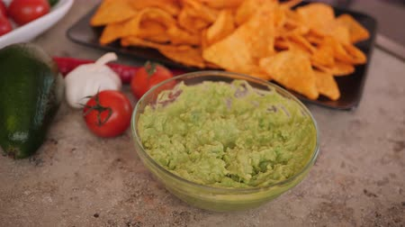 Hands scoop guacamole sauce with delicious tortilla chips - static camera Stok Video