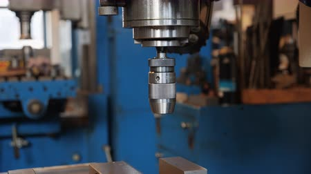 Industrial drilling machine in metal workshop - close up of the drill head, camera orbit
