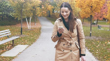upřímný : Woman uses her smartphone while taking a walk on a beautiful fall day. 4K footage.
