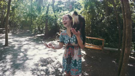 monkey : Funny shot of a woman trying to take a selfie with a monkey on her shoulders but it tries to look down her top.