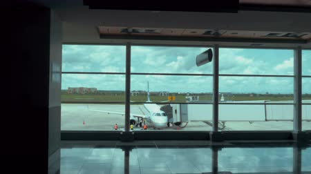 Ванкувер : Establishing shot of a fully boarded airplane as viewed through a gate window. 4K footage. Стоковые видеозаписи