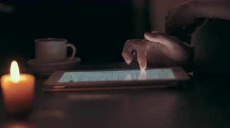 slider shot : Woman using a tablet pc on coffee table at home late at night. Low key shot. Stock Footage