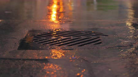 drenar : Rain falling in slow motion down a sewer drain at night in the city.