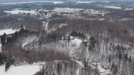 doorgeven : Aerial establishing shot of a curvy secluded road during the winter. Cinematic 4K footage.