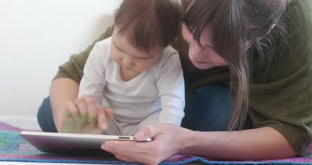 Young Mother using Tablet with her Baby Daughter. 4K Cinematic Footage.