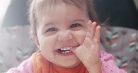 ten : Portrait of happy baby girl chewing on her thumb. Stock Footage