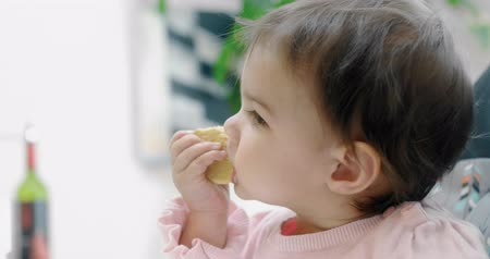 невинность : Baby girl attemtping to eat a cookie by herself. Cinematic 4K footage. Real life, not staged.