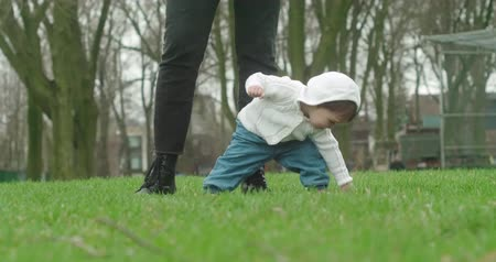 Little baby girl learns to walk with the help of her mother. Real life, candid 4K footage. Wideo