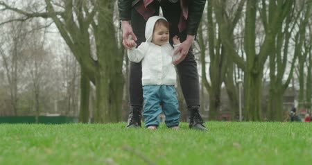Little baby girl learns to walk with the help of her mother. Real life, candid 4K footage. Stock mozgókép
