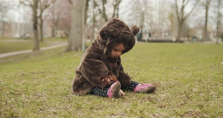 невинность : Adorable baby girl at the park dressed as a bear. Cinematic 4K footage. Стоковые видеозаписи