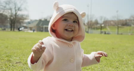 Adorable baby girl at the park dressed as a bear. Cinematic 4K footage. Wideo