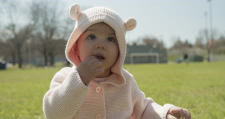 suçsuzluk : Adorable baby girl at the park dressed as a bear. Cinematic 4K footage. Stok Video