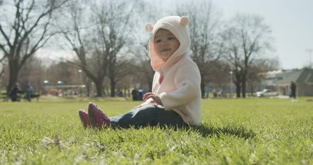 Adorable baby girl at the park dressed as a bear. Cinematic 4K footage. Stok Video