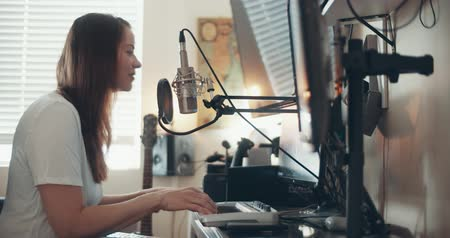 Young woman recording a track in her home studio. Cinema 4K footage. Stock mozgókép