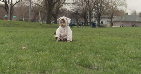 Portrait of a cute baby girl being silly in a dog costume at a park. 4K footage.