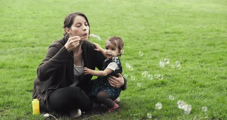 Mother blowing bubbles with baby girl. Cinematic 4K footage.