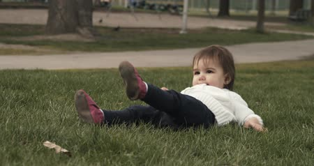 Cute baby girl exploring a park in late spring. Real life, candid 4K footage.