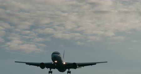 Cinematic shot of a passenger jet airplane about to land. 4K telephoto shot.