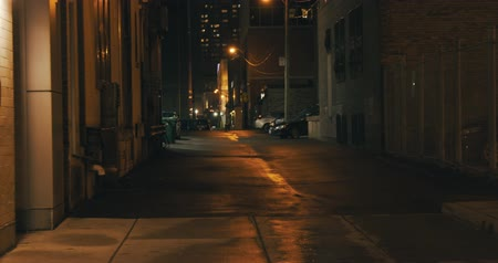 uliczka : Establishing shot of a dark alleyway at night. Atmospheric 4K footage. Shot on a cinema camera in RAW. No discernible faces or logos.