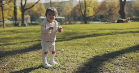 Super cute baby girl playing in the park. Shot in 4K RAW.