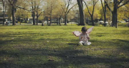 Baby girl dressed in fairy wings playing in the park. Shot in 4K RAW.