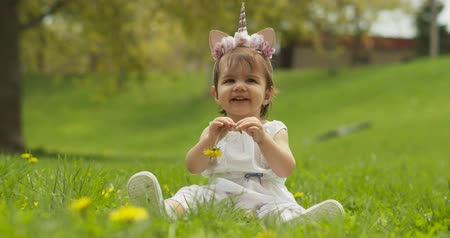 Adorable baby girl at the park dressed as a unicorn. Shot in 4K RAW on a cinema camera. Stock Footage