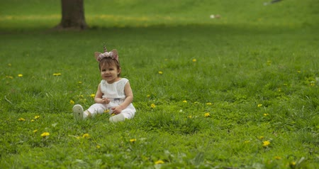 beatiful : Adorable baby girl at the park dressed as a unicorn. Shot in 4K RAW on a cinema camera. Stock Footage