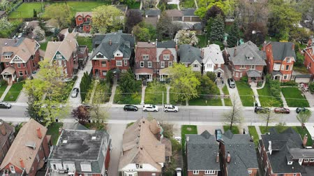 Aerial view of residential homes in late spring. Cinematic 4K establishing shot.