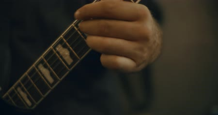 rocker : 4K Closeup of fingers playing an electric bass guitar in a home studio. Cinematic footage.