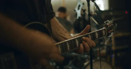 gitáros : 4K Closeup of fingers playing an electric guitar in a home studio. Cinematic footage.