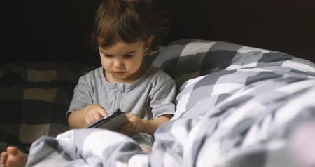 concentrando : One year old girl using tablet in bed. Cinematic 4K footage.