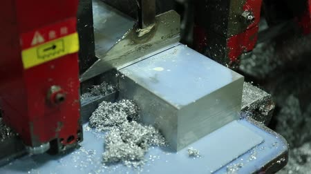 metal worker : Cutting Aluminum Flat Bar on Bandsaw production workshop for metalwork, where there is a band saw equipment, lubricating emulsion and oil very slowly saws off material from the raw billet Stock Footage