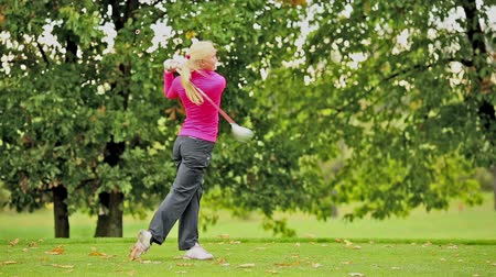 поле для гольфа : Young female golf player hitting the ball Стоковые видеозаписи