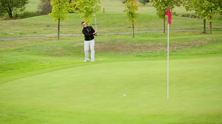 swing : Young male golf player hitting the ball Stock Footage