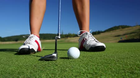 поле для гольфа : The Putting Green. Close-up view of a female golf player as she puts under-par on the Green.