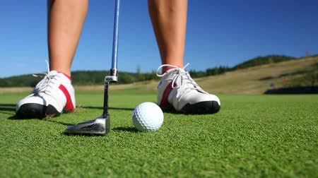 swing : The Putting Green. Close-up view of a female golf player as she puts under-par on the Green.
