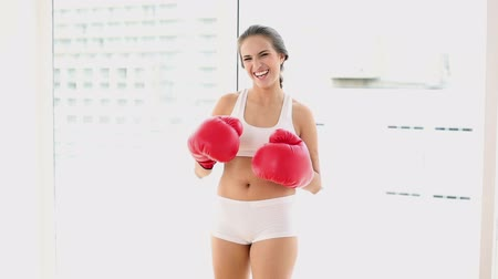 boxe : Beautiful young woman punching with red boxing gloves at home in a bright room