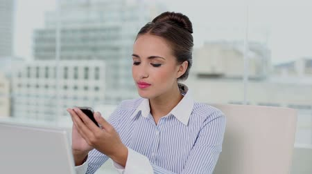 amarrado : Young businesswoman sending a text at her desk in her office