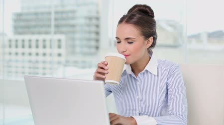 amarrado : Young businesswoman working on her laptop drinking coffee in her office